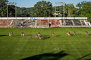The Aliquippa High School football team walks across Carl A. Aschman Stadium from the practice field following practice to prepare for their homecoming game on September 16, 2015 in Aliquippa, Pennsylvania, USA.<br /> <br /> The fans still come in droves and sit in bleachers with rusting steel and wooden bleachers to watch their beloved school's football team play in a stadium that was built in 1937.<br /> <br /> The school has one of the smallest enrollments in the Western Pennsylvania Interscholastic Athletic League (WPIAL) with the class of 2013 having only 58 kids, including 28 boys.<br /> <br /> Pretty steep obstacles for a coach and team to overcome, but the team averaged 10 wins a year for the past 30 years. The team was the training ground to NFL greats like Mike Ditka, Sean Gilbert, and Ty Law, all of whom were Aliquippa graduates.