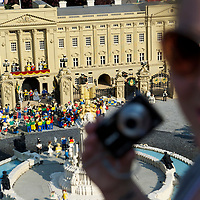 Tourists huddle around a miniature display of Buckingham Palace and the royal wedding in LegoLand, the day after the royal wedding of Prince William and Kate Middleton at Westminster Abbey.