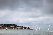The Solent Sunbeam fleet racing under inclement skies on the opening day of Aberdeen Asset Management Cowes Week. The event began in in 1826 and plays a key part in the British sporting summer 'season'. It now stages up to 40 daily races for around 1,000 boats and is the largest sailing regatta of its kind in the world with 8,500 sailors competing.<br /> Picture date Saturday 2nd August, 2014.<br /> Picture by Christopher Ison. Contact +447544 044177 chris@christopherison.com