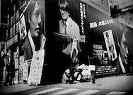 Homeless man perched on a busy corner in Shinjuku, Tokyo, Japan.