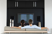 Couple sitting in front of flat screen television in living room back view