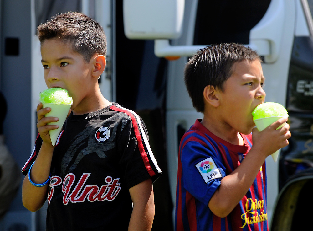 jt071417a/ a sec/jim thompson/left to right- Jesus Chavez-8 and Andre Batres-7 enjoy some snow cones at Rotary Park in Bernalillo,NM  as they attend the Cops in the Park celebration. Friday,  July. 14, 2017. (Jim Thompson/Albuquerque Journal)