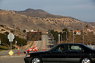 A car drives past an illuminated display on Sesnon Blvd. warning would be burglars that the LAPD is in the area and to encourage residents - many who have moved out of their homes - to call 911 if they see criminal activity, as methane gas leaks from the SoCalGas Aliso Canyon Storage Facility well SS-25 in the Porter Ranch neighborhood of Los Angeles, California on Sunday, January 3, 2016. The Aliso Canyon gas leak (also called Porter Ranch gas leak) was a massive natural gas leak that started on October 23, 2015. According to Wikipedia, an estimated 1,000,000 barrels per day was released from a well within the underground storage facility in the Santa Susana Mountains near Porter Ranch. The second-largest gas storage facility it belongs to the Southern California Gas Company (SoCalGas), a subsidiary of Sempra Energy. On Jan. 6, 2016, Governor Jerry Brown issued a State of Emergency. The Aliso gas leak carbon footprint is said to be larger than the Deepwater Horizon leak in the Gulf of Mexico. On Feb. 11, 2016 the gas company reported that it had the leak under control. On Feb. 18 state officials announced that the leak was permanently plugged. An estimated 97,100 tonnes of methane and 7,300 tonnes of ethane was released into the atmosphere, making it the worst natural gas leak in U.S. history in terms of its environmental impact. © 2016 Patrick T. Fallon