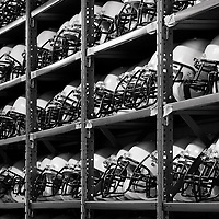A rack of kids football helmets lines the wall of a storage building near the Vienna Community Center waiting for the football season to begin, Vienna, Virginia.