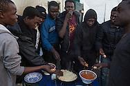 Calais, Pas-de-Calais, France - 17.10.2016    <br />  <br /> Eritrean refugees share a porridge dinner. &rdquo;Jungle&quot; refugee camp on the outskirts of the French city of Calais. Many thousands of migrants and refugees are waiting in some cases for years in the port city in the hope of being able to cross the English Channel to Britain. French authorities announced that they will shortly evict the camp where currently up to up to 10,000 people live.<br /> <br /> Eritreische Fluechtlinge essen gemeinsam ein Haferbrei Abendessen. &rdquo;Jungle&rdquo; Fluechtlingscamp am Rande der franzoesischen Stadt Calais. Viele tausend Migranten und Fluechtlinge harren teilweise seit Jahren in der Hafenstadt aus in der Hoffnung den Aermelkanal nach Gro&szlig;britannien ueberqueren zu koennen. Die franzoesischen Behoerden kuendigten an, dass sie das Camp, indem derzeit bis zu bis zu 10.000 Menschen leben K&uuml;rze raeumen werden. <br /> <br /> Photo: Bjoern Kietzmann