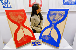 © Licensed to London News Pictures. 05/10/2019. LONDON, UK. A visitor next to giant rubber stamps by artist Savvas Verdis depicting Donald Trump, US President, and Borish Johnson, Prime Minister, each within an hourglass at The Other Art Fair, presented by Saatchi Art.  120 international, independent artists are displaying their works to be sold direct to buyers.  The fair is taking place at Victoria House in Bloomsbury until 6 October 2019.  Photo credit: Stephen Chung/LNP