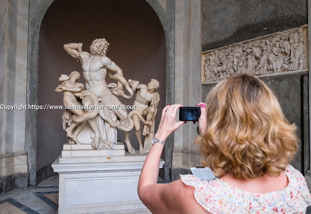 Tourist looking at The Laocoön group sculpture at the Vatican Museum in Rome, Italy