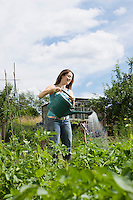 Young woman watering plants in garden