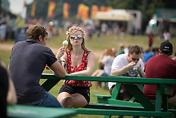 Image ©Licensed to i-Images Picture Agency. 18/07/2014  Henham Park , Suffolk, United Kingdom. A woman eats an ice cream at Henham Park on what is forecast to be the hottest day of the year so far with temperatures due to hit 30 degrees centigrade. The Latitude Festival of music and arts. Picture by Joel Goodman / i-Images
