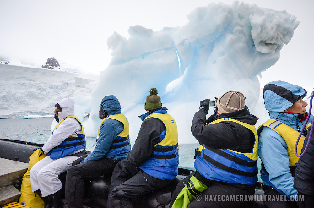 A group of tourists cruise on the side of an inflatable boat past an a small iceberg in Curtis Bay, Antarctica.