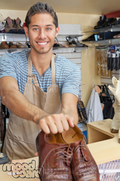Portrait of young man giving handmade shoes