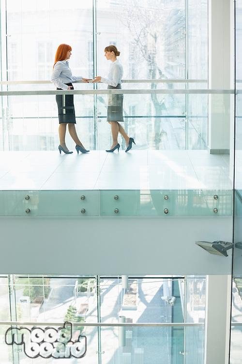 Full-length of businesswomen conversing in office