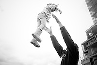 a father tosses his young daughter in the air