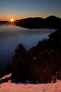 The sun peaks over the crater's rim, casting Crater Lake in the warm glow of sunrise, Crater Lake National Park, Oregon