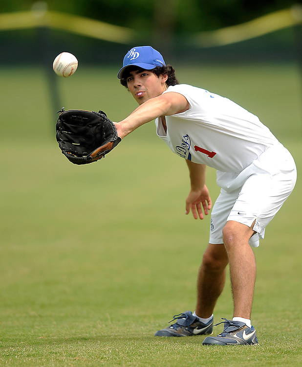 "AUGUST 19, 2009 BOCA RATON FLORIDA- Joe Jonas, of the Jonas Brothers, catches a ball as he warms up in preparation for his game against the Marquis Flyers. The Jonas Brothers and their team, the ""Road Dogs"" took part in the softball game which was being held by Marquis Jet at the Saint Andrews School in Boca Raton, Fla. Marquis Jet has held 9 other softball games around the country as their company team the ""Marquis Flyers"" competes in for fun games against various teams. PHOTO BY JOSH RITCHIE"
