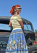An attractive Rockabilly girl posing in front of a Hotrod car, Viva Las Vegas Festival, Las Vegas, USA 2006.