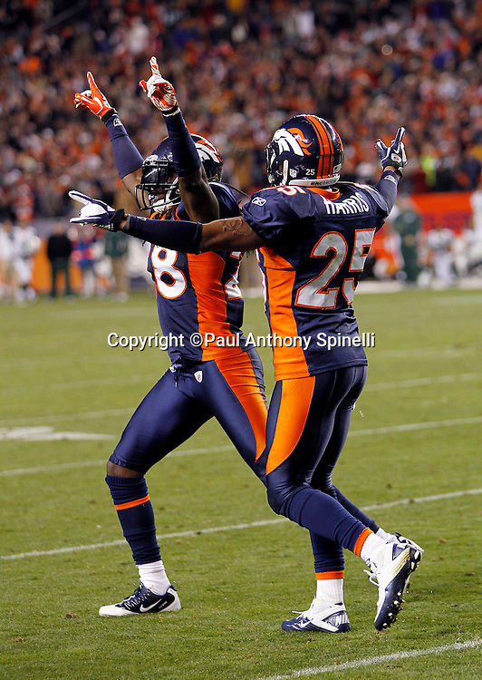 Denver Broncos free safety Quinton Carter (28) and Denver Broncos strong safety Chris Harris (25) raise their arms in celebration after breaking up a Hail Mary pass at the end of the NFL week 11 football game against the New York Jets on Thursday, November 17, 2011 in Denver, Colorado. The Broncos won the game 17-13. ©Paul Anthony Spinelli