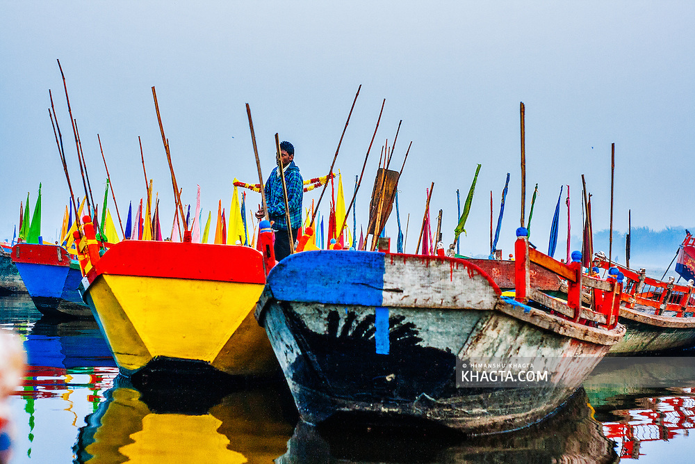 A boatman with his colorful boats on Yamuna river in Mathura. Mathura is a sacred town situated on the banks of Yahuman river in Uttar Pradesh, northern India. The birthplace of the deity Lord Krishna. It is a pilgrimage site for Hindus.