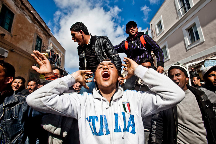 People fleeing unrest in Tunisia protest in the streets of Lampedusa. Italian Prime Minister Silvio Berlusconi promised to clear thousands of illegal Tunisian migrants from Lampedusa by the weekend after an outcry over a humanitarian crisis on the tiny southern island