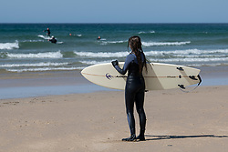 © Licensed to London News Pictures. 04/04/2020. Surfer looks out at the other surfers enjoying the surf. Surfing at Perranporth beach during the coronavirus lockdown. Cornwall UK. . Photo credit: Mark Hemsworth/LNP