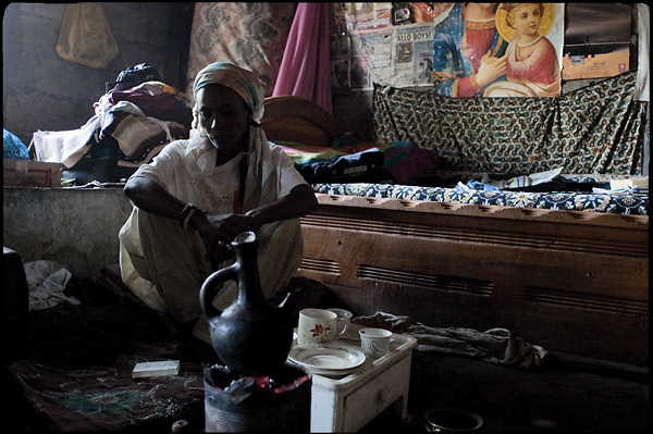 """ZH, a 32 years old ethiopian woman of rastafarian faith, during the coffee's rite in his small room. She lives with her daughter in a garage, a part of a quite big compound, received as a gift from the Twelve Tribe of Israel, as member of the movement. Shashemene, south Ethiopia, on wednesday, March 19 2008.....""""Shashamene or Shashemene (ethiopian name), located in the Oromia Region of Ethiopia, is """"the place"""", the ancestral homeland. For the whole Rastafarians repatriation to Africa or to Zion or to the Promise Land is the first goal. Rastas assert that """"Mount Zion"""" is a place promised by Jah and they  claim themselves to represent the real Children of Israel in modern times. During the last years of the 40's, Emperor Haile Selassie I, considerated from that movement incarnation of God, donated 500 acres of his private land to members and other settlers from Jamaica including other parts of the Caribbean..The Rastafarian settlement in Shashamane was recently reported to exceed two hundred families. In January 2007 it organized an exhibition and a bazaar in the city. It was also reported recently prior to the Ethiopian Millennium that various pro-Ethiopian World Federation groups, consisting of indigenious Ethiopians and Rastafarians, have given support to one of many five year plans proposed for sustainable development of Shashamene, Ethiopia."""""""