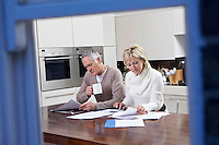Middle-aged couple reading documents in kitchen