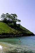 Man on the beach in Lagoa Azul (Blue lagoon) with baobab trees on a hill. Lagoa Azul is on the north coast of Sao Tome island.