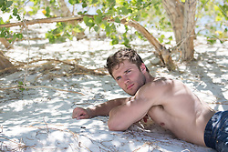 All American shirtless man resting under trees
