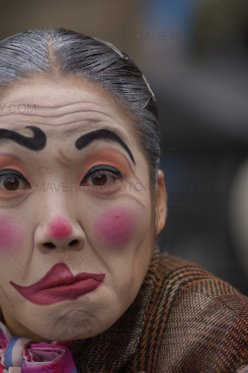 Edinburgh International Festival and Fringe performers entertain crowds on the High Street.  Pictured a woman with a painted clown face..