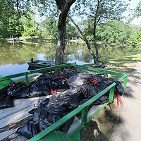 Hundreds of dead fish fill garbage bags ona trailer after they have been removed from a lake on Strain Street in Tupelo Tuesday morning.