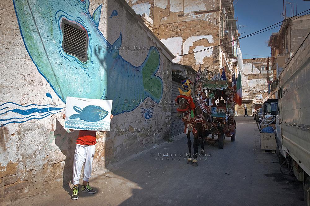 Palermo, quartiere Borgo vecchio, periferia degradata nel cuore della citt&agrave;.un bambino mostra il disegno che ha ispirato il murales.<br /> Palermo: &quot;Borgo Vecchio district&quot; deprived suburb within the heart of the city, a child shows the original drawing that inspired the murales