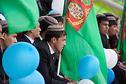Male university students dressed in suits and tahyas (national Turkmen hats), watch horse racing from the granstand of the City Hippodrome in Ashgabat on the occasion of National Turkmen Horse Day