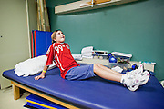 30 DECEMBER 2009 -- PHOENIX, AZ:  Mackenzie Saunders (CQ) stretches during physical therapy at St. Joseph's Hospital in Phoenix Wednesday. Mackenzie was knocked down by another player during a soccer game. She finished the game but later in the day her legs started hurting and her parents took her to a hospital. Three hospitals later, she was in St. Joseph's with a diagnosis of a swollen spine and she couldn't walk. Now she's in physical therapy. She is expected to make a full recovery but her doctors have said she won't be able to play soccer for at least another 16 months.   Photo by Jack Kurtz
