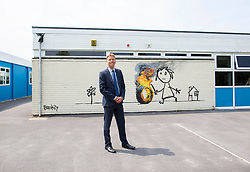 © Licensed to London News Pictures. 06/06/16. Bridge Farm headteacher Geoff Mason next to recent artwork by graffiti artist Banksy on the side of Bridge Farm Primary school in Bristol. Photo credit should read Brad Wakefield/LNP