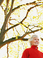 Portrait of a mature woman with tree in background.