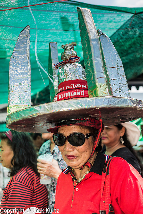 01 MAY 2013 - BANGKOK, THAILAND:    Thai Red Shirts, including a woman wearing a model of Thailand's Democracy Monument as a hat, line up for lunch during the Red Shirt rally at the Thai Constitutional Court. Several hundred Thai Red Shirts, members of the United Front for Democracy against Dictatorship (UDD), have been camped out at Thailand's Constitutional Court, which oversees matters related to the Thai constitution and constitutional amendment. The Red Shirts are protesting the court's decision to consider a petition regarding the constitutionality of the constitutional amendments that have been proposed by the government. The group is arguing that by considering the petition, the Court is impeding the powers of the legislative branch.  PHOTO BY JACK KURTZ