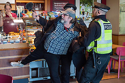 © Licensed to London News Pictures. 10/10/2019. London, UK. An Extinction Rebellion protester is grabbed and removed from a cafe after trying to evade police as other protesters block the entrance to London City Airport. Protesters arrived via the Docklands Light Rail and proceeded to conduct a sit-in to block the entrance from the train station to the airport. Photo credit: Peter Manning/LNP