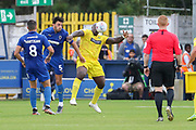 AFC Wimbledon defender Will Nightingale (5) battles for possession with Wycombe Wanderers attacker Adebayo Akinfenwa (20) during the EFL Sky Bet League 1 match between AFC Wimbledon and Wycombe Wanderers at the Cherry Red Records Stadium, Kingston, England on 31 August 2019.