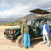 A safari guide and cook pose next to their Toyota Landcruiser on the floor of the Ngorongoro Crater in the Ngorongoro Conservation Area, part of Tanzania's northern circuit of national parks and nature preserves.