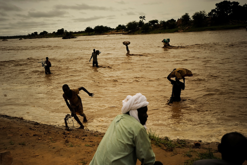 Locals cross a flooded riverbed in a rural area two hours outside of Abéché, Chad.