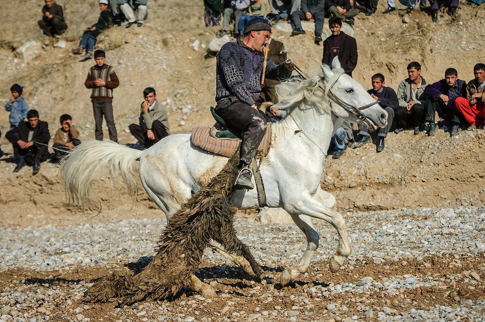 Image of a Tajik horseman charging off with the buz (a stuffed goat) toward the finish at a buzkashi event in the village of Kostarosh, northwest Tajikistan