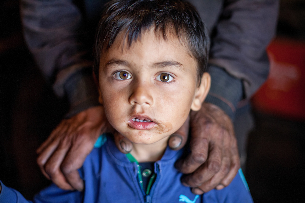 Portrait of a child with the hands of the local blacksmith at the Roma area in Frumusani.