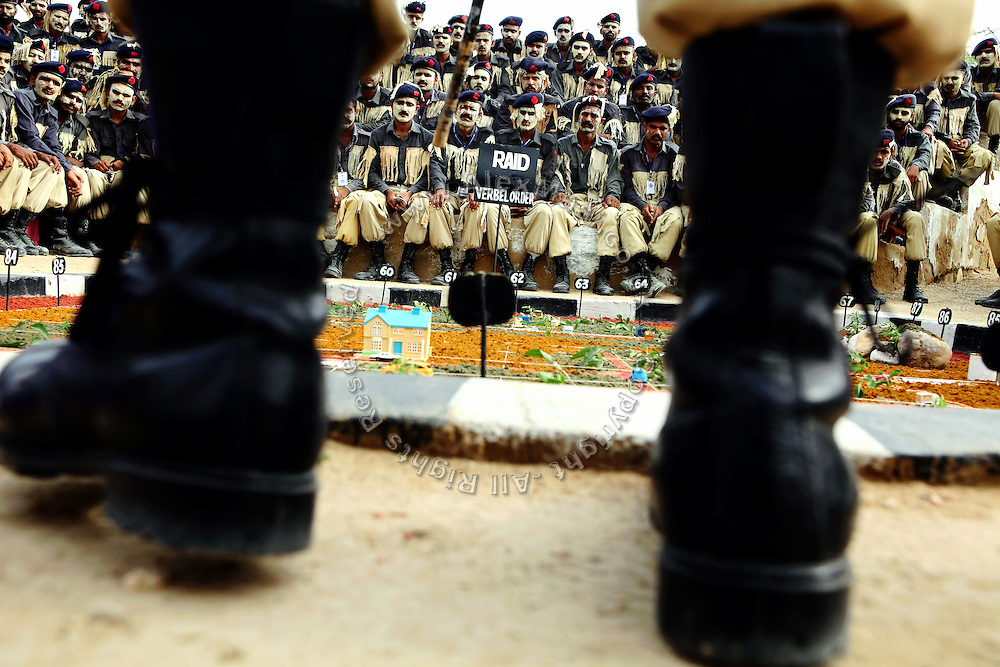 Recruits of the the Shaheed Benazir Bhutto Elite Police Training Center, a commando and anti-terrorism academy on the outskirts of Karachi, are being briefed on raids and security procedures. The training center was founded by retired colonel Abdul Wahid Khan, a brave officer who served as a gunship helicopter pilot in the Pakistani Air Force and around the globe with the United Nations, but who's first task as a young army officer in 1979 was to train Afghan Mujahedeen to fight the Soviet Army, the very Mujahedeen that are today's Taleban.