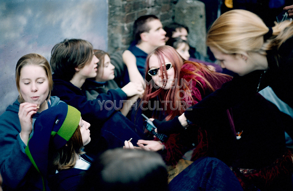 a group of Nu metal teenage boys and girls sitting in a group in Camdem Town London Uk 2001