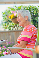 Smiling mature woman sitting outside on patio.