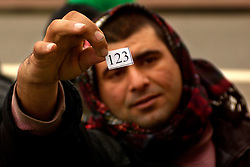 CALAIS, FRANCE - DEC -31-2002 - A refugee holds up his number as he stands in the rain on new years eve day waiting for food which is distributed daily by local aid organizations. Food was in short supply due to the new year holiday which caused tensions to run high between the refugees. The refugees were given numbers in an effort to make sure everyone received food.