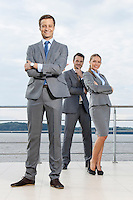 Full length portrait of confident businessman standing with coworkers on terrace against sky