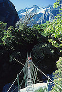 A tramper (hiker) crosses a swing bridge on the Copeland Track, West Coast, South Island, New Zealand. 1981 photo. In 1990, UNESCO honored Te Wahipounamu - South West New Zealand as a World Heritage Area.