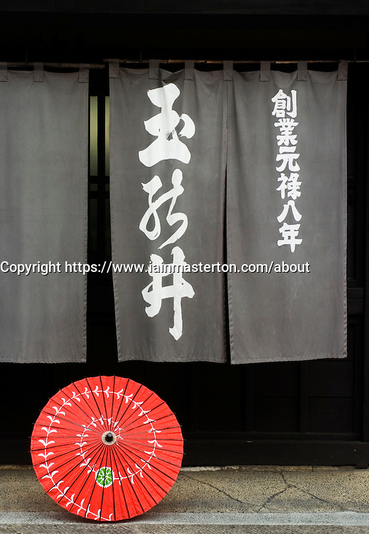 Detail of curtain and red parasol outside traditionl shop in historic town of Takayama in Japan