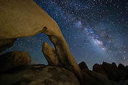 Normally I like to explore a location during the day before taking pictures there at night. But the Southern California traffic robbed me of the time to do that here. Arch Rock was a little bit hard to find in the dark, but it wasn't too bad. I just had to be careful to avoid rattlesnakes. The 30 foot long arch is located near the White Tank campground in Joshua Tree National Park. The eastern part of the park has very dark skies the farther you get from the desert cities. To illuminate the scene, I shined my headlamp on the rock wall opposite the arch. A soft, warm light was reflected backwards. I was grateful the skies cleared up long enough to see the milky way. A few minutes after this clouds started to cover the sky as monsoon thunderstorms moved past the area.<br /> <br /> Date Taken: August 19, 2014